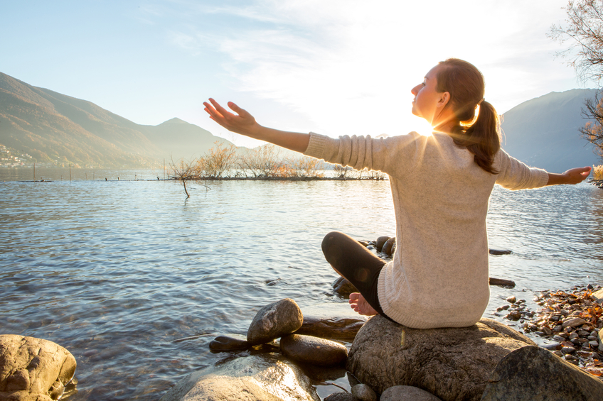Young cheerful woman by the lake exercising yoga at sunset.