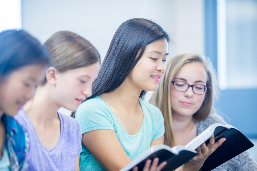 A high school age girl is holding the Bible and is reading it with her fellow classmates during a Bible study.