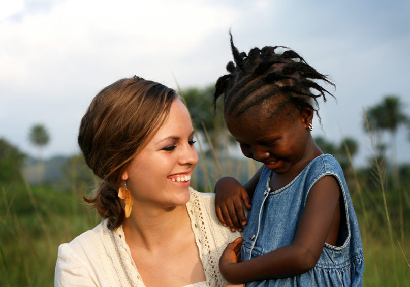 A pretty young lady from America laughing with a cute little girl from West Africa.