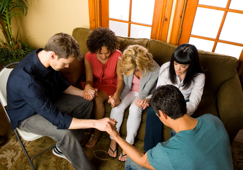 A diverse group of young people in their 20's and 30's praying together holding hands