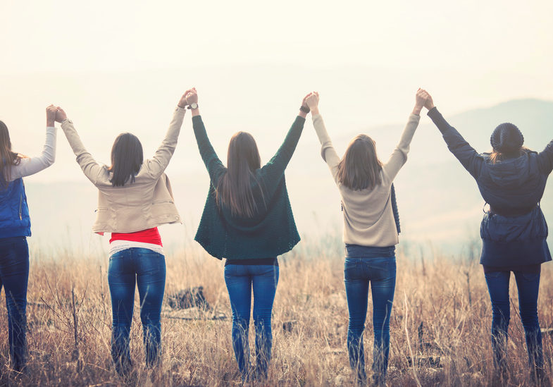 Group of female friends holding hands on a hilltop and looking at view
