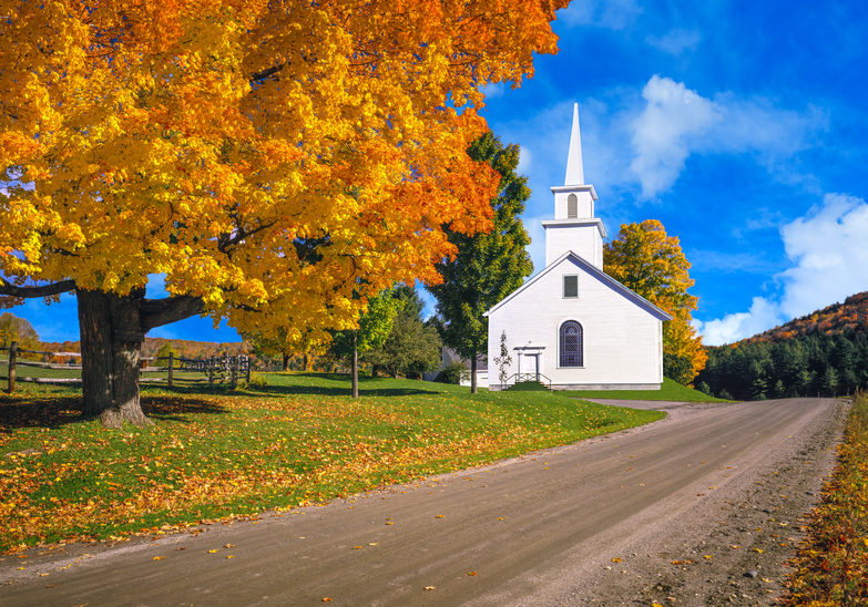 A large sugar maple in full autumn color and a country church fill the foreground leading back to the country side of the Green Mountains, Vermont