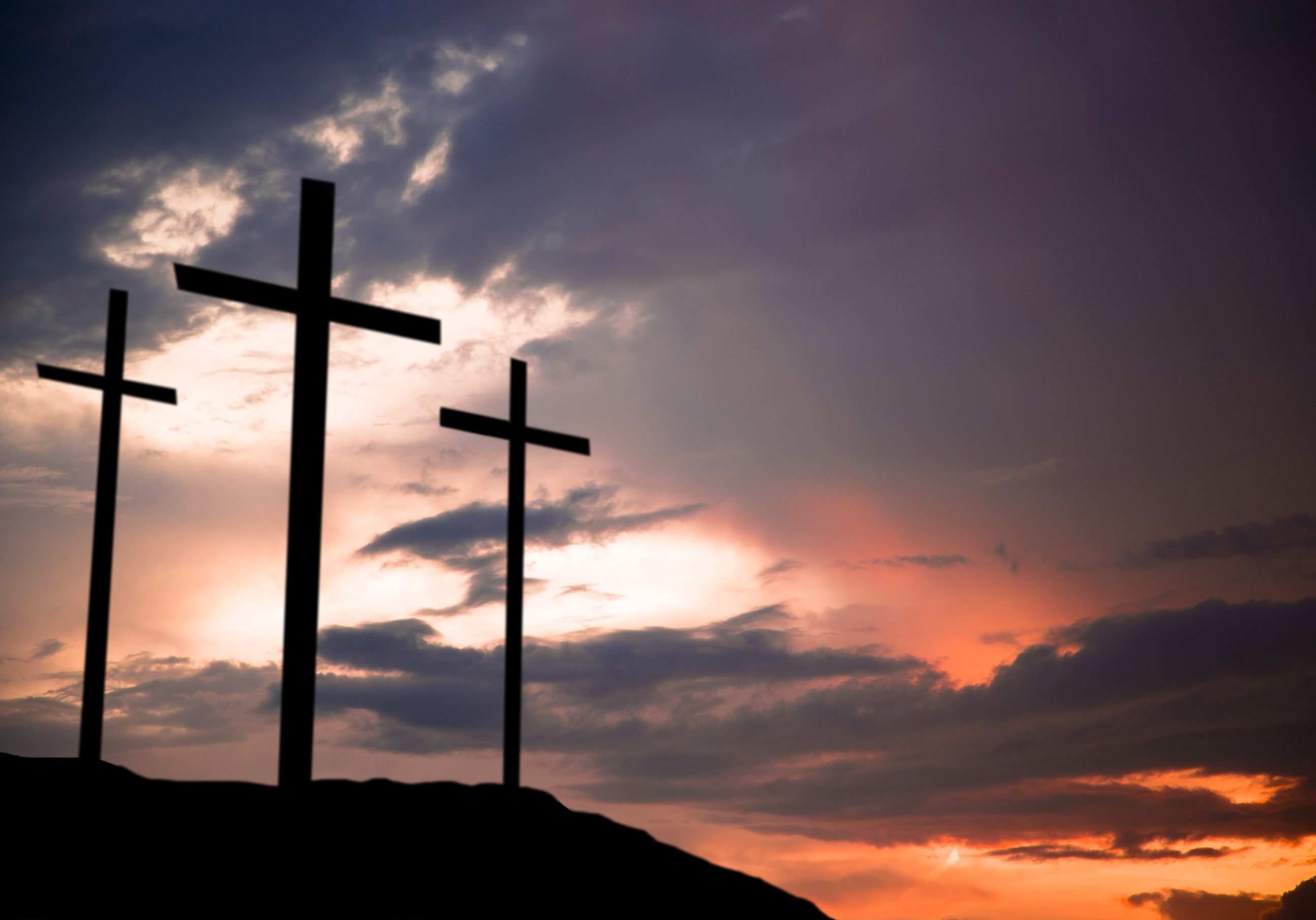 Easter.  The crucifixion.  Three wooden crosses in silhouette stand silently on a hill at sunset.  The dramatic sky is beautiful in its purple and orange colors.  Christianity, religious themes. Copyspace.