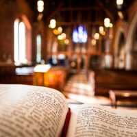 Bible open at the book of John inside an Anglican Church of England church. The focus is on the foreground of the bible, while in the background, defocused, are the pews and arches of the historic eighteenth century building. Horizontal colour image with copy space.
